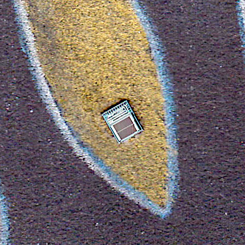 small rectangular silicon chip sitting on gold graphite background