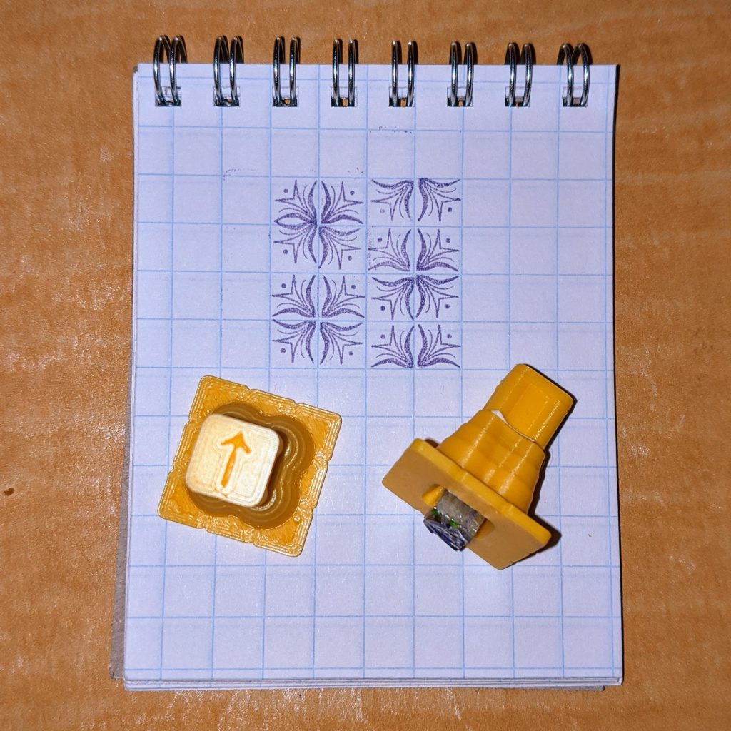 squared pad with floral imprints and metal type in plastic holders