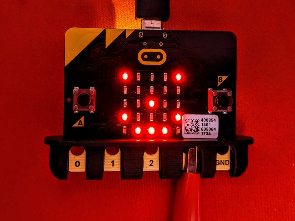 micro:bit educational electronic board with a small 3d-printed comb-like device protecting the contacts from alligator/croc clips shorting