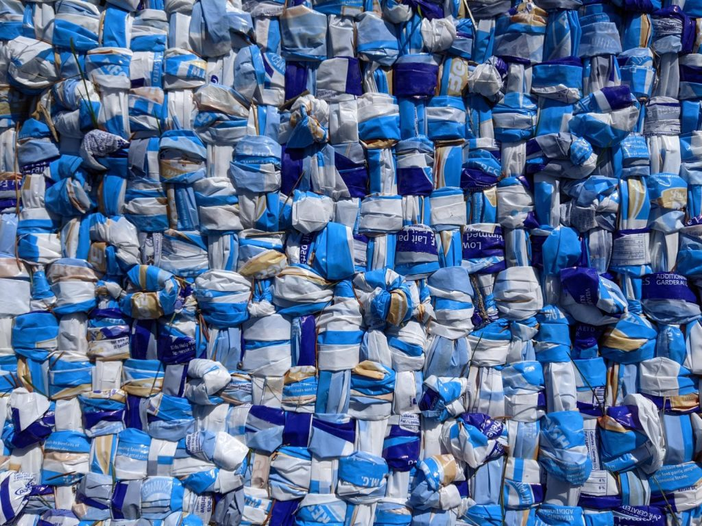 blanket woven from hundreds of milk outer bags: dark blue, light blue, white, yellow. Appears to be from Beatrice 1% 4 litre bags
