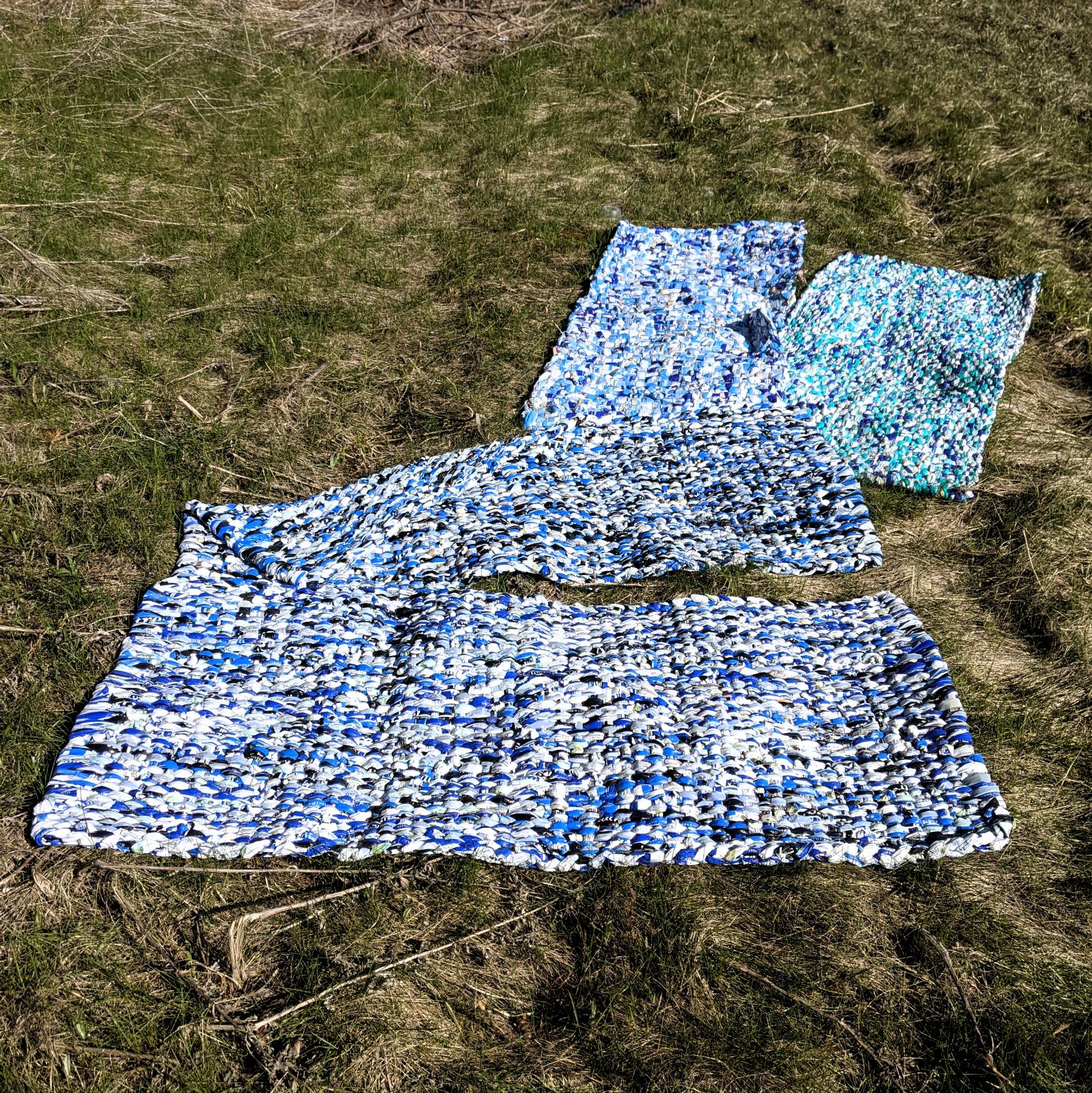 blankets woven from hundreds of milk outer bags: dark blue, light blue, white, yellow. Mats are laid out on tussocky grass