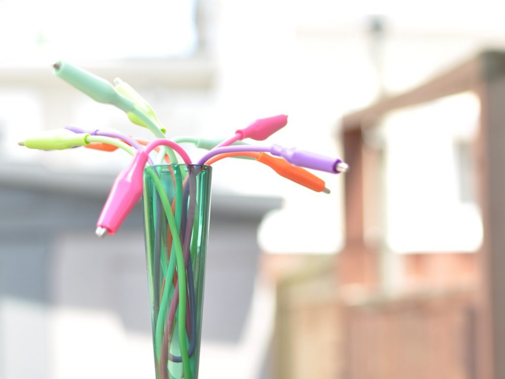 multi-colour alligator clips arranged in a green bud vase as if they were flowering buds, high-key natural light