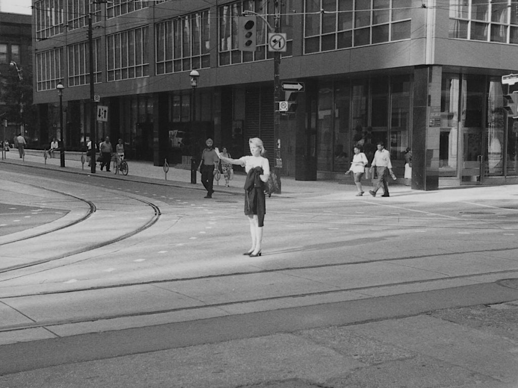 A woman in business attire stands in the middle of a downtown street. It is late afternoon on 14th August 2003, the first day of the blackout. She is facing west along a street with streetcar lines: her shadow from a beam of sunlight from between two buildings is prominent behind her. Her dark jacket is folded over her left arm, and her right arm is extended in a Stop gesture. No traffic is visible, but there are many pedestrians visible behind her